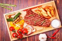BBQ stek z piec na grillu warzywami na tnącej desce Zdjęcie Stock