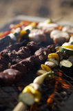 Bbq sticks. Bbq stick (veal) on the hot grill with fruits and vegetables stock photos
