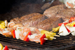 Bbq surf and turf. Grilling shrimp kabobs and steaks on the bbq on a sunny afternoon stock photos