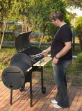 BBQ Time. Man cooking bbq meat on the grill stock photography