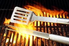 BBQ Utensils and Hot cast iron grate XXXL. BBQ Utensils lie on the Hot cast iron grate surrounded by flame, you can also see more pictures of BBQ on my page stock image