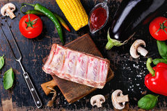 BBQ vegetables background. Concept BBQ background with uncooked pork ribs, assortment of raw vegetables, herbs, barbecue sauce, salt and meat fork over old black Stock Image