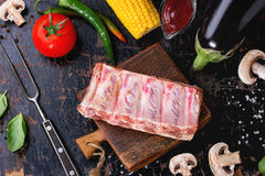 BBQ vegetables background. Concept BBQ background with uncooked pork ribs, assortment of raw vegetables, herbs, barbecue sauce, salt and meat fork over old black Stock Images