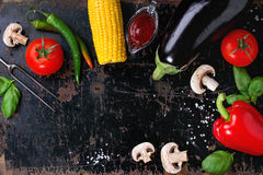 BBQ vegetables background. Concept veggie BBQ background with assortment of raw vegetables, herbs, barbecue sauce, salt and meat fork over old black wooden Royalty Free Stock Image