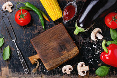 BBQ vegetables background. Concept veggie BBQ background with assortment of raw vegetables, herbs, barbecue sauce, salt, small chopping board and meat fork over Stock Photos