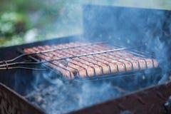 BBQ worsten die bij de grill worden gekookt Stock Afbeelding