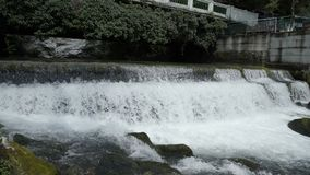 Bbridge over fast mountain river river with waterfall. View of a fast moving river with rapids. stock footage