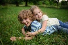 Bbrother e a irmã jogam em um gramado verde fotografia de stock royalty free