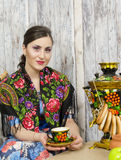Bbrunette sitting at the samovar with bagels. Beautiful brunette sitting at the samovar with bagels Royalty Free Stock Image