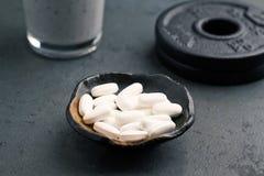 BCAA amino kwasy, szkło proteinowy potrząśnięcie z mlekiem, borówki i talerze, Odżywianie dla bodybuilding Sprawność fizyczna nad zdjęcia stock