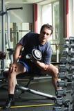 Bíceps del entrenamiento del hombre con pesa de gimnasia Fotografía de archivo libre de regalías