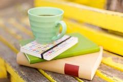 Bücher und Schale auf Holztisch Stockfotografie