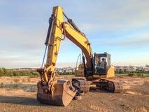 Bêcheur d'excavatrice garé sur un chantier Photographie stock libre de droits