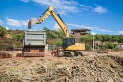 Bêcheur d'excavatrice remplissant camion Photographie stock