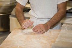 Bäcker, der Brot, Mannhände, einen Teig knetend macht und kochen Mantel Lizenzfreie Stockfotos