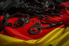Bdsm toys for pain and pleasure. Laying on german flag stock photo