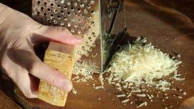 Beëindigend grating een kaas op rasp door zon wordt verlicht die