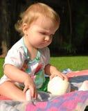 Beísbol con pelota blanda conmovedor del niño y mirada de la hierba Imagen de archivo libre de regalías