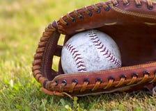 Beísbol con pelota blanda gastado en mitón Foto de archivo