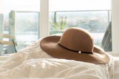 Beżowy kobiety round słońca kapelusz z kwiecistym podstrzyżeniem i szeroki rondo na puszystym comforter w sypialni z balkonem w t obrazy royalty free