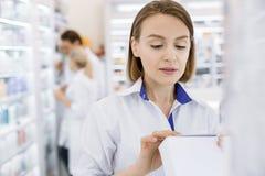 Meditative female pharmacist studying medication stock images