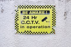 Be aware 24 hr hour CCTV security camera in operation yellow sign on white wall. Of private office accommodation stock images