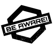 Be Aware rubber stamp. Grunge design with dust scratches. Effects can be easily removed for a clean, crisp look. Color is easily changed Stock Photography