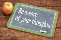 Be aware of your thoughts. Inspirational words on a slate blackboard against red barn wood royalty free stock photography