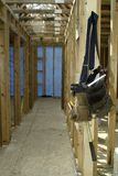 Be Back Later. Tool belt hanging on the interior framing studs in a hallway of a house under construction Royalty Free Stock Photography