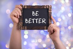 Be better. A woman holding chalkboard with words be better on bokeh light background stock image
