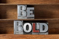 Be bold tray. Be bold phrase made from metallic letterpress type on wooden tray royalty free stock images