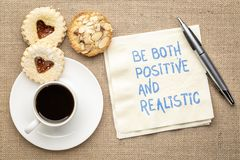 Be both positive and realistic. Inspiraitonal handwriting on a napkin with a cup of coffee and cookies royalty free stock photos