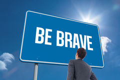 Be brave against sky. The word be brave and businessman standing with hand on hip against sky stock images