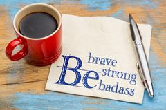 Be brave, strong and badass. Be brave, be strong, be badass - handwriting on a napkin with a cup of coffee Stock Image