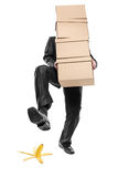 Be careful. Person with paper boxes about to step on a banana peel Royalty Free Stock Photo