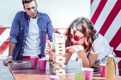 Close up of pretty brunette girl that leaning on table. Be careful. Charming female expressing positivity while playing table game in group of her friends royalty free stock photo