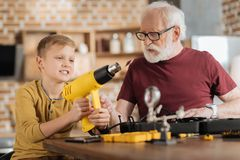 Happy young boy playing with a drill Royalty Free Stock Images