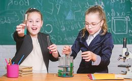 Be careful performing chemical reaction. Basic knowledge of chemistry. Girls study chemistry. Make studying chemistry. Interesting. Educational experiment stock photo