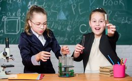 Be careful performing chemical reaction. Basic knowledge of chemistry. Girls study chemistry. Make studying chemistry. Interesting. Educational experiment royalty free stock images