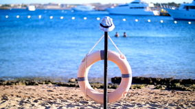 Be careful in the water, saving life on the water, lifebuoy. A sandy beach, a summer day on the Red Sea, in the foreground a life ring is seen, and someone left stock video footage