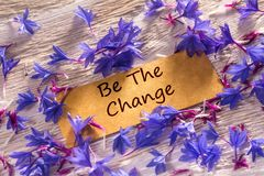 Be The Change. In looking memo on white wood with beautiful blue flowers around stock photo