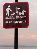 Be considerate sign. Urging dog owner to leash their pet and to pick up their pet's poo Royalty Free Stock Photography