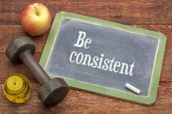 Be consistent concept - slate blackboard sign. Against weathered red painted barn wood with a dumbbell, apple and tape measure stock photos