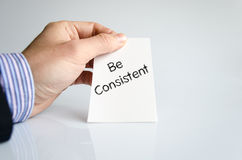 Be consistent text concept. Be consistent note in business man hand royalty free stock photography