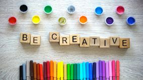 Be creative phrase made of cubes, colorful felt-tip pens and paints lying table. Stock photo royalty free stock images