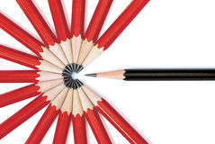 Be Different. Close up of a black pencil standing out from a circle formed by the tips of several red pencils. Isolated on white