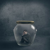 Be ermetic. Concpet with a businessman closed in a jar Stock Images