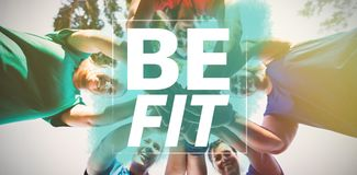 Composite image of be fit. Be fit against directly below shot of women stacking hands at camp Royalty Free Stock Photo