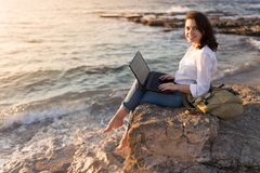 Be free, work whenever you want. Freelancer girl working on the beach royalty free stock images