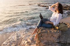 Be free, work whenever you want. Freelancer girl working on the beach stock images
